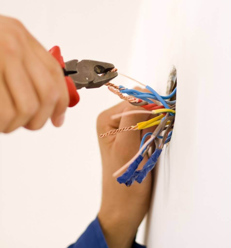 Electrician's hands using tool to cut wires in a wall