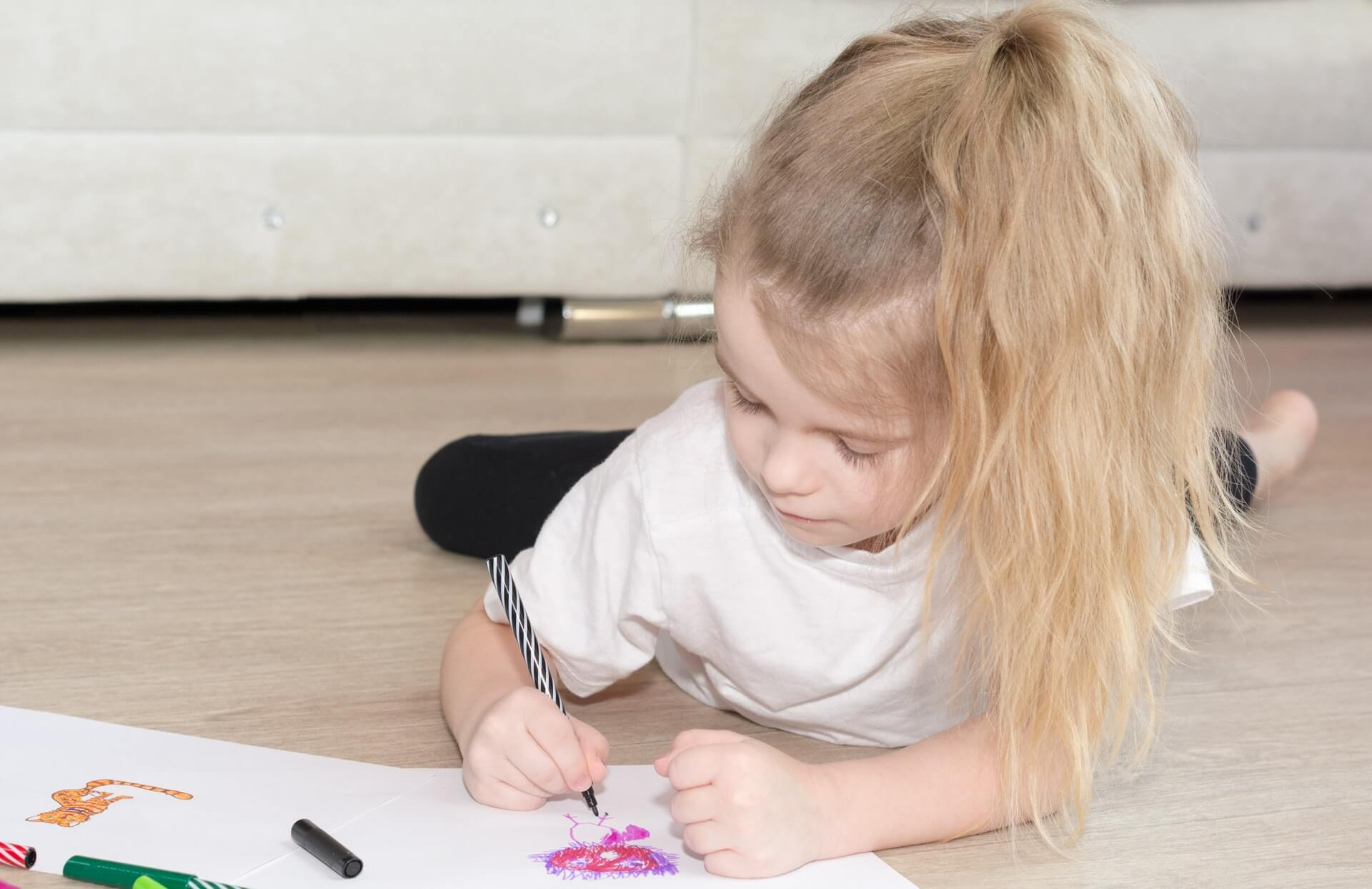Picture of a young girl lying on a heated floor and drawing pictures