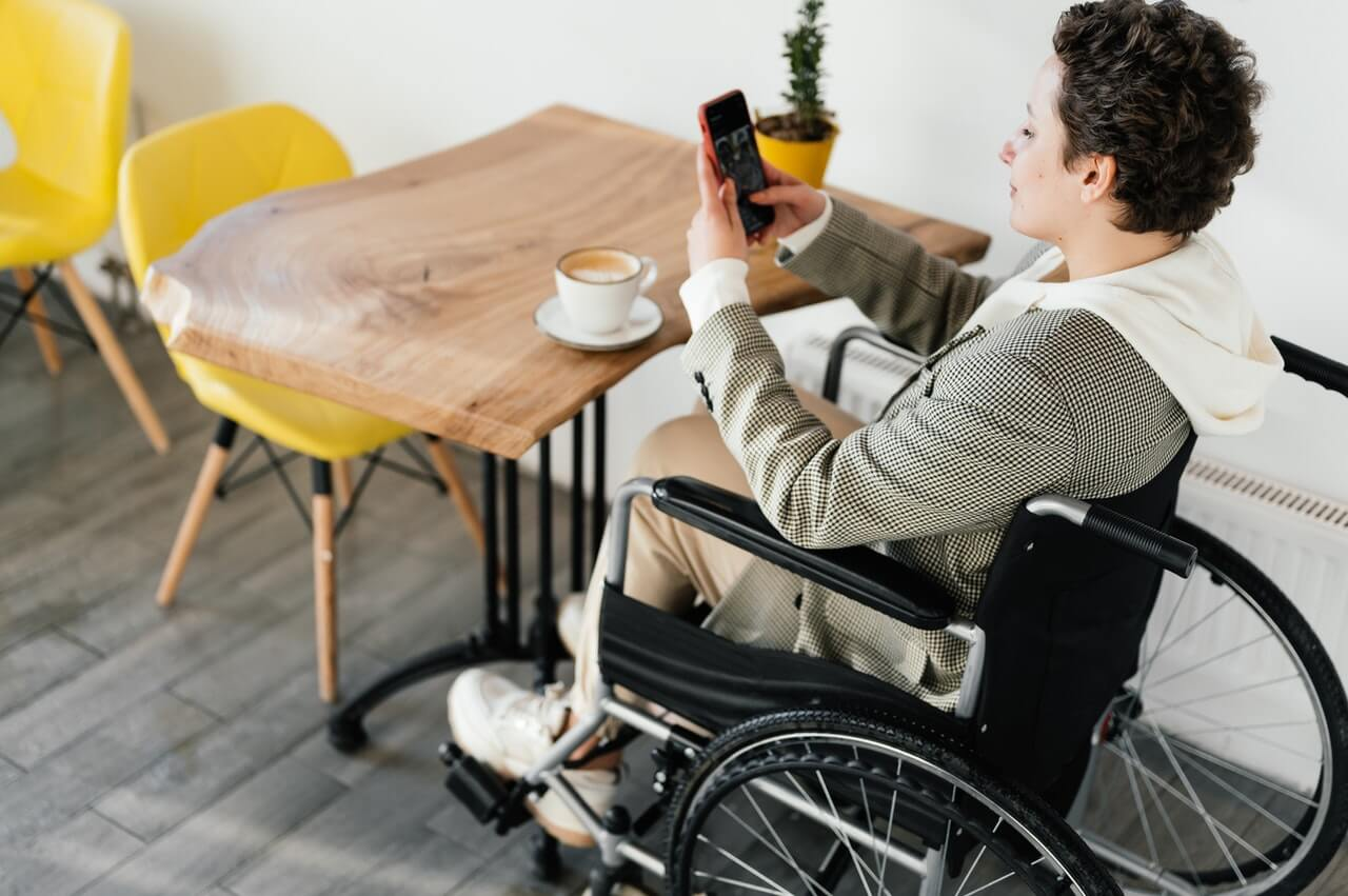 Picture of a lady in a wheelchair using a smartphone app
